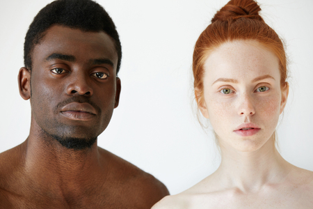 amigos abrazandose: Love against racism. Black and white. Coffee and milk. Headshot of young loving multi-ethnic couple standing shirtless against white studio wall, looking at the camera. African man and Caucasian woman
