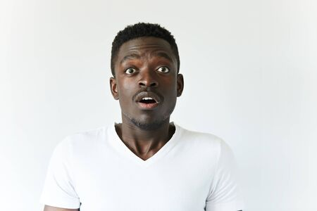 unforeseen: Portrait of shocked dark-skinned student or employee in casual clothes, looking at the camera with surprised expression, astonished with some unexpected news, mouth wide open. Body language