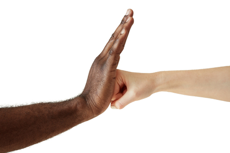 african solidarity: Two people of different races and ethnicities holding hands in handshake expressing friendship, solidarity and cooperation. White Caucasian woman throwing a punch at the open palm of black African man