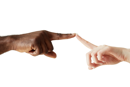 racial: A white womans hand and black mans hand touching with the tip of a finger. White woman and black man holding fingers together in world unity, racial love and understanding against white studio wall