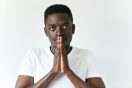 african worship: Close up portrait of handsome young African man praying isolated against white background. Dark skinned student wearing white T-shirt, holding hands in prayer against his lips, hoping for the best Stock Photo