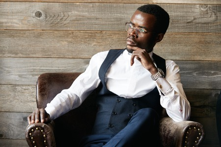 hard day at the office: Successful young dark-skinned entrepreneur in formal clothing, sitting in leather armchair against wooden background, thinking and making plans for future, while relaxing after hard day in the office