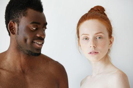 Portret van gelukkige liefdevolle interracial paar: shirtless Afrikaanse mens die zijn naakt roodharige blanke meisje met liefde en genegenheid, terwijl ze naast hem en kijken naar de camera