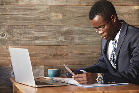 work took: Young and successful businessman looking at contract and reading information in documents with blue pen in hand. Focused African man took laptop and digital devices with wi-fi for productive work.