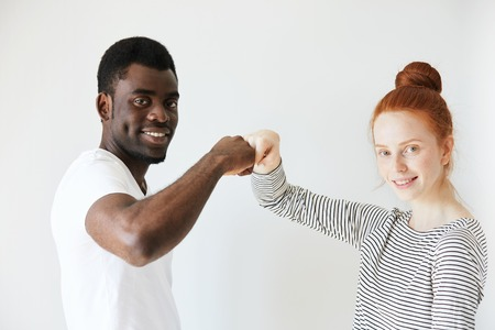 contended: Side view portrait of youngster salutating each other with bumping fists. Caucaisan redhead girl smiling at camera with her African American friend or coworker, showing positive emotions and peace. Stock Photo