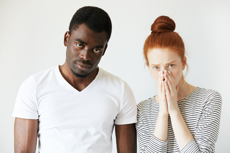 sorting out: Mixed-race relationships. Interracial couple: Redhead Caucasian woman covering her face and African man in white T-shirt looking at the camera, sorting out their relationships, thinking about divorce.