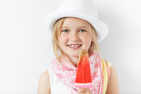 contended: Blond child with contended smile and yummy lollipop looking forward with joy and natural simplicity. Nothing could be better than summertime free atmosphere, sweets, sunshine and happy kid. Stock Photo