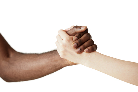 african solidarity: Multiracial handshake between black African man and white Caucasian woman. Two people holding hands in respect and solidarity against white wall background. Interracial friendship and cooperation Stock Photo