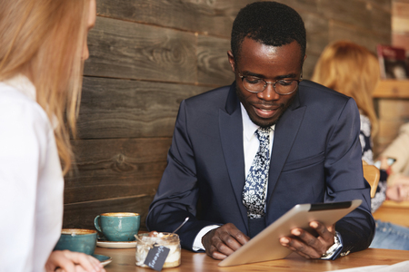 sitted: Team work: two business people in formal wear sitting together at the table and discussing something. African man using digital tablet during a business meeting with his Caucasian female partner Stock Photo
