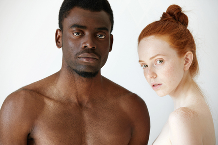 naked african: Multi-ethnic love and relationships concept: young redhead Caucasian woman wearing no clothes standing next to her naked African boyfriend, looking at the camera with serious expression on their faces
