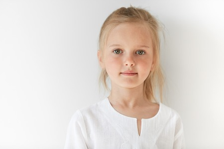innocent: Little European girl in white children clothes looking peacefully at the camera indoors. Calm child standing quietly in restful manner with angelic look and innocent appearance.