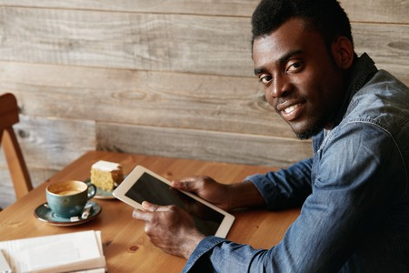 denim wear: Portrait of handsome black student in denim wear, looking at the camera with happy expression while enjoying leisure time at a coffee shop, using electronic device after classes at university