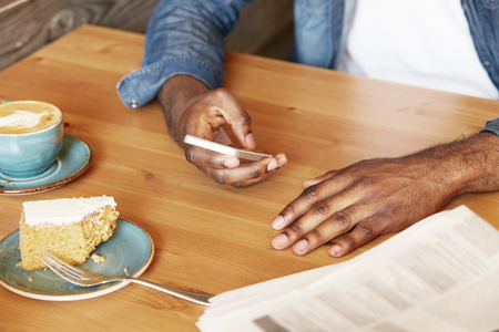 american dessert: Selective focus. Portrait of African American man wearing denim jacket typing a message or checking email on smart phone while spending leisure time having cappuccino and dessert at a restaurant