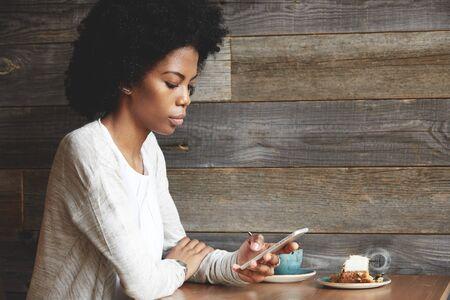 Portrait de jeune femme séduisante noir avec Afro coiffure en utilisant la connexion Internet haut débit, envoyant ses amis via les réseaux sociaux sur téléphone intelligent, assis à un café contre le mur en bois