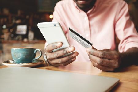 Homme afro-américain en chemise casual payer par carte de crédit en ligne tout en faisant des commandes via Internet. Succès transaction d'affaires de fabrication de noir à l'aide de l'application bancaire mobile. mise au point sélective Banque d'images