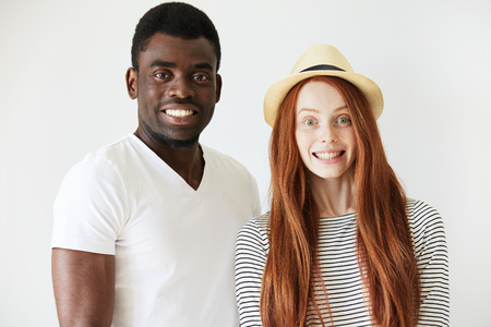 fake smile: Full face portrait of young couple deliberately smiling at camera in white studio. Red-head girl with hat staring forward with tight and fake smile, Afro American man pretending to smile too.