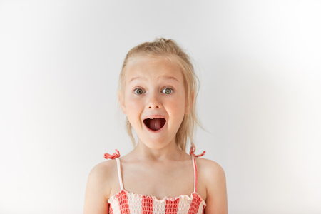 trustful: Little European girl opening mouth in surprise and raising her eyebrows with wonder. Blond child with naive glance, trustful simplicity and amazed face.