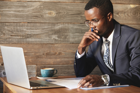 perplexed: Serious African American businessman looking at laptop screen and thinking upon problem while sitting in coworking cafe. Perplexed dark-skinned man in round glasses covered up his mouth with hand. Stock Photo