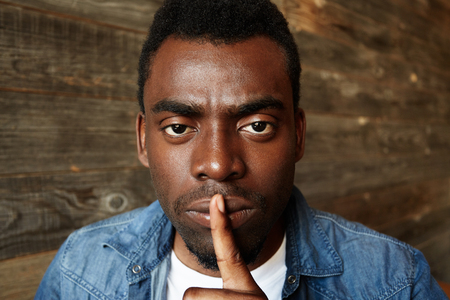 hushed: Headshot of young African man in stylish clothes holding finger on lips, asking to be quiet or keep silence, saying shh, looking at the camera with serious and concentrated expression. Body language