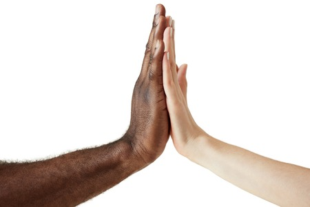 Blanco hembra de raza caucásica y el concepto de sexo masculino de la mano juntos en la unidad del mundo, el amor y la comprensión racial afroamericano negro. Cierre de tiro de dos personas de diferentes culturas que dan cinco.