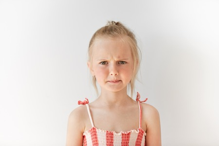 displeasure: Small female child looking seriously at camera in white studio. Blond girl with pony-tail frowning eyebrows and screwing up her mouth in reproach. Negative emotions, displeasure, offence.