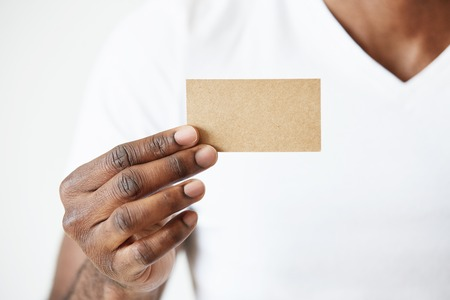 identity card: Confident African entrepreneur in white T-shirt giving business card to you. Close up view of black male hands holding blank business card for your information or promotional content. Selective focus