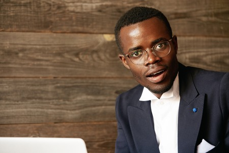 distant work: Handsome dark-skinned corporate worker in formal suit and glasses using laptop for distant work while sitting at the hotel lobby, looking at the camera in shock, surprised with sensational news