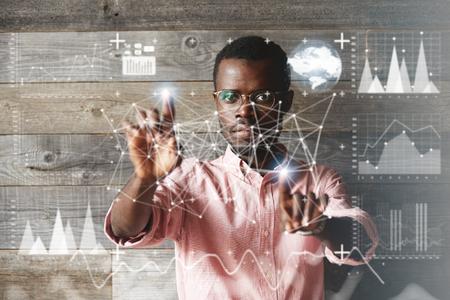 Visueel effect. Wereldwijde interface. Geconcentreerde Afrikaans-Amerikaanse programmeur die aan een project werkt, afbeeldingen en diagrammen maakt, futuristische scherminterface aanraakt. Selectieve focus op het gezicht
