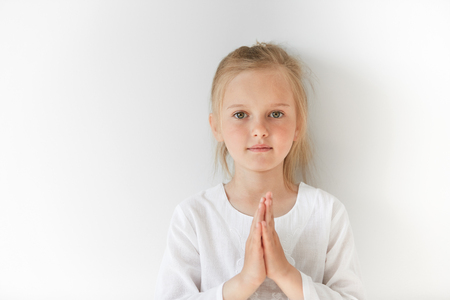Little European girl in white clothes praying and looking forward with calm and pretty facial expression. Blond child with green eyes watching you peacefully in morning light.