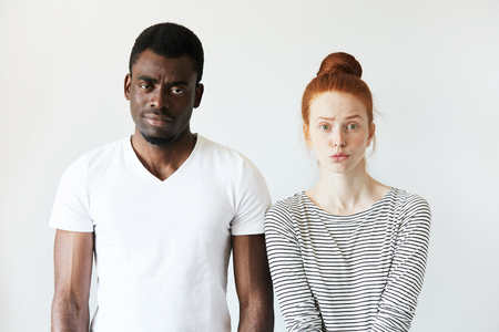 interracial love: Interracial love and friendship. African male and redhead Caucasian woman looking at the camera with disappointment, having quarrel, displeased with each other. Portrait of young mixed-race couple