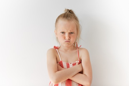 bad temper: Portrait of Caucasian kid with blond hair and crossed hands on her chest. Angry female child with spoiled look demonstrating bad vibes. Negative emotions and offence.