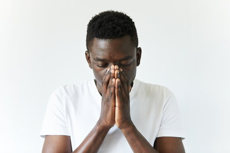 Close up shot of African man wearing white T-shirt standing with depressed and sad look, covering his face, thinking of something bad happened, hoping for the best. Human face expressions and emotions