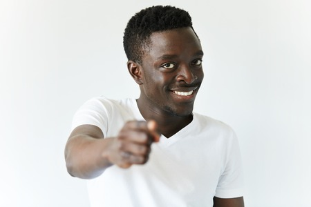Headshot of young dark-skinned employee or customer in casual clothes pointing a finger at the camera, choosing you, looking and smiling with cheerful face expression. Body language. Film effect