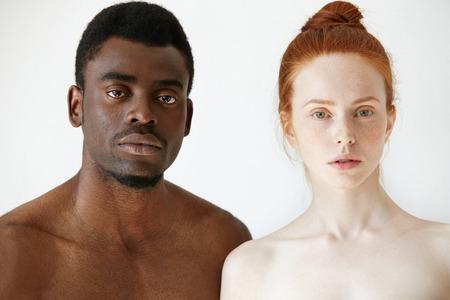 さまざまな人種の若い人の間の真の愛。そばかすの赤毛白人女性とアフリカ人の人、白いコンクリートの壁の背景に裸のポーズ、カメラ目線のヘッ