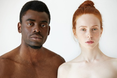 True love between two young people of different races. Headshot of freckled redhead Caucasian woman and African man posing shirtless against white concrete wall background, looking at the camera Stockfoto