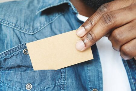 out of business: Close up view of black male holding blank card. Young African businessman pulling out business card from pocket of his denim jacket, exchanging information with a potential partner. Film effect