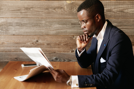 Handsome young African entrepreneur reading financial news in morning paper with confident concentrated look, resting his elbow on the wooden table in the cafe, sitting against wooden wall background