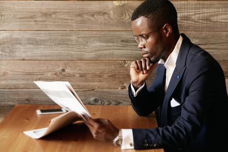 Knappe jonge Afrikaanse ondernemer het lezen van financieel nieuws in de ochtend papier met vertrouwen geconcentreerde blik, rust zijn elleboog op de houten tafel in het cafe, zittend tegen de houten wand achtergrond Stockfoto - 58980489