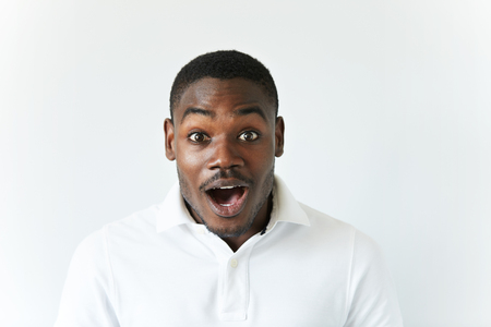 Portrait of excited African American screaming and looking at the camera in excitement, surprised with some positive news, mouth wide open. Human face expressions and emotions, body language