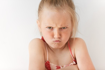 conflicted: Small girl with blond pony-tail looking seriously, folding hands and frowning eyebrows. Her gloomy appearance says she is very unhappy and offended. Blond baby showing disapproval with pursed lips.