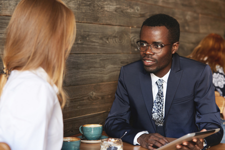 eyecontact: Young African businessman holding tablet and sharing data with female Caucasian colleague during coffee break in cosy caf?. Smart coworker makes an eye-contact with job partner and listens to her.