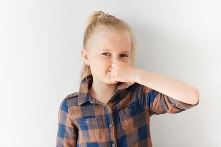 stench: Little girl in checked brown shirt pinching her nose because of bad smell. Blond kid standing in white light room with disgusting facial expression. She is unhappy with stench and looking at camera.