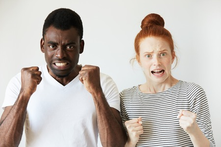 bunched: Redhead girl and African man standing indoors with fist bunched and face screwed. The man is so raged as if ready to fight, the girl is horrified and frowning her eyebrows with negative emotions. Stock Photo