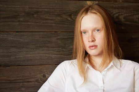innocent: Full face beautiful portrait of beautiful and young Caucasian girl on wooden background. Blond office woman in white shirt staring attentively at camera with relaxed face and peaceful emotions.