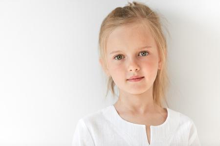 niños rubios: Niña bonita con rasgos caucásicos mirando peacfully y de pie todavía como niño obediente. Ella se ve hermosa, atractivo, agradable, amable y de buenos modales. Foto de archivo