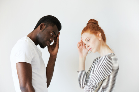 dissapointed: Sideways portrait of couple in disappointed pose in white studio. Caucasian girl resting her head on her hand as if thinking and solving the problem, African man also looking puzzled and stressed.