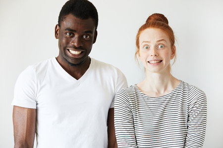 freezed: A couple grinning and making scary faces with false smiles and wide eyes. African man staring at camera and red-head Caucasian girl is freezed in stupefaction. Strange and crippy mimics, fun concept. Stock Photo