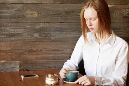 hard day at the office: Student girl with ginger hair sitting at the table at a cafe, enjoying coffee and eating dessert after classes at college. Young female office worker relaxing at a coffee shop after hard day at work