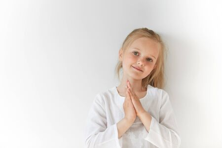 Portrait of European blond kid smiling and folding hands like a prayer. Her total white look and charming face show her positive emotions, purity, simplicity, friendly attitude and peace.