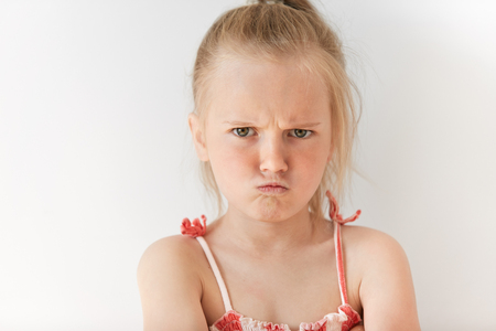 Close up portrait of disobedient child demanding attention. Little Caucasian girl feeling aggravated, naughty and stubborn. With her mischievous behavior she looks wicked. Stock Photo